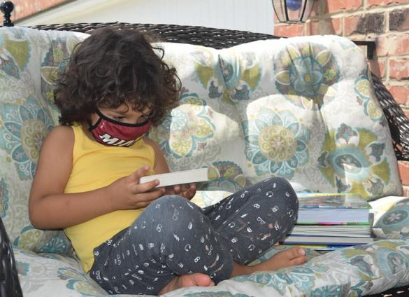 A child reads books from Charlotte Mecklenburg Library at home.