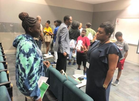 """A Charlotte Mecklenburg student engages in conversation with a careerwoman during the Library's """"Bigger than High School"""" event in July, 2019."""