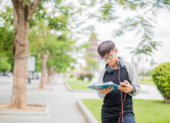 A young person reads poetry from Charlotte Mecklenburg Library on a mobile device.