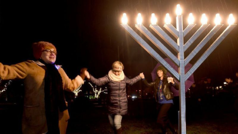 Photo of people dancing around a Hanukkah menorah courtesy of the Chicago Tribune